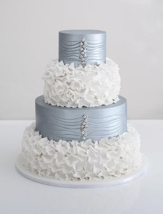 white petal-like fondant with silver pearls going down the center of the cake.