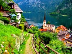 Hallstatt - Austria - Austria, beautiful, fence, grass, green, hallstatt, houses, lake, lovely, mountain, nature, peaceful, reflection, river, roofs, slope, stones, villahe, water
