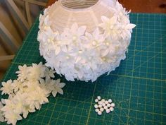DIY Tutorial looks like the  Ikea paper lantern, cheap Michael's garland, some pom pom's --- Glue on the flowers.