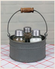 """Round Bucket Salt and Pepper and Toothpick Caddy 36.00  This cute tin caddy includes three mason jar shakers.  One is for your salt, one is for your pepper and the one with the two holes is a toothpick holder for those warm nights out on your picnic table eating sweet corn on the cob!  What could be cuter?  5 x 5 x 2.5"""""""