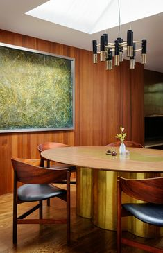 Incredibly glamorous midcentury modern dining room design with warm wood paneled walls