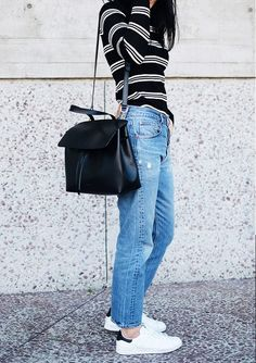 Andy Heart wears a striped t-shirt, vintage jeans, a Mansur Gavriel Lady Bag, and Adidas Stan Smith sneakers