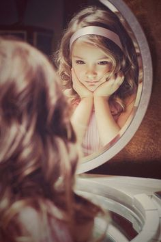 Females always look for praises and compliments from their mirror as the mirror never lies. It even speaks out the hidden truth which eyes of many can't see. The correctly posed doll like girl standing in front of mirror is truly adorable and looks as her best.