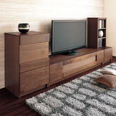 木の塊のようなテレビボード。突板をガラス表面に貼り木枠で組み上げることで、外観は板材で組み上げた質感なのに、扉を閉めたままでもリモコン操作が可能に。ウォールナットの木目も美しく充実機能のテレビ台。