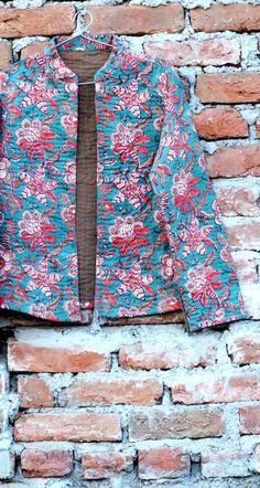 A trendy quilted block print blue jacket with red motifs.  A short cut to SMART look!!