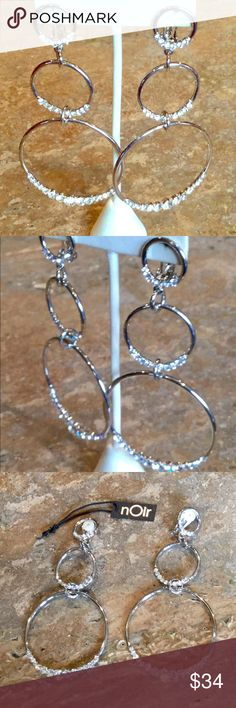 "Noir Silvertone 3 Circle Bling Clip On Earrings ""NOIR"" BOLD AND SPECTACULAR SILVERTONE TRIPLE CIRCLE BLING EARRINGS  ""GORGEOUS""  Not for the shy at heart! Decorate your outfit with this incredibly luscious earrings! These bold earrings will become a brilliant addition to your jewelry wardrobe!  - Silvertone  - Clear Austrian Crystals  - Clip-On  - Measures 4-1/2""L x 2""W  Perfect Gift!! nOir Jewelry Jewelry Earrings"
