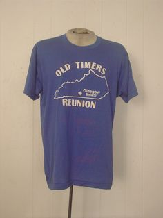 Vintage 1980s t-shirt. Made of blue poly/cotton. Reads: OLD TIMERS REUNION GLASGOW KENTUCKY. Label reads: SCREEN STARS XL. Actual measurements are:  44 around the chest,  44 around the waist, 20 shoulder seam to shoulder seam, 30 overall length. In good condition. Faded on front and back.