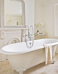 Elegant Neutral Bathroom with Roll-top Bath and Large Mirror