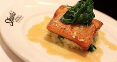 Rosemary Honey-Mustard Glazed Salmon with Watercress Crab Risotto, Sautéed Spinach and Apple Cider Reduction at Shula's Steak House at The Saucon Valley Promenade Shops. Located in Center Valley, PA