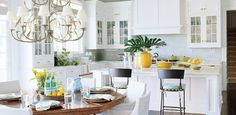 Light, bright open kitchen design with white glass-front kitchen cabinets, calcutta marble counter tops, subway tiles backsplash, kitchen island, chandelier, octagonal dining table and white slipcovered dining chairs.