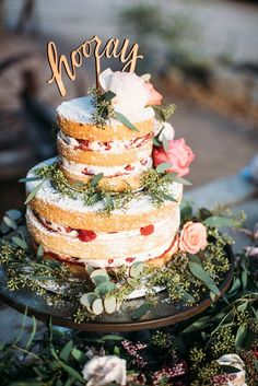 """two tiers rustic wedding cake with greenery and gold """"hooray"""" cake topper"""