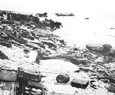 Omaha Beach. Debris of the landing assault on Dog Beach, with discarded life preservers most prominent. Boxes of demolitions in foreground.