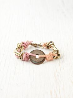 two-tone suede wrapped chain link bracelet w/distressed coin pendant detailing. Lobster claw clasp closure. By Dannijo