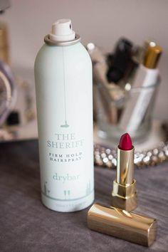 lápiz de labios colocado junto a una botella de laca para el cabello