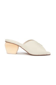 A peep toe shoe that will undoubtedly pass the tests of time. Made of  smooth off-white leather with a wooden block heel, these stunning slides  almost look like they're carved from clay. Pair with a midi dress and head  to your nearest garden party or art gallery opening. --     * By Intentiona