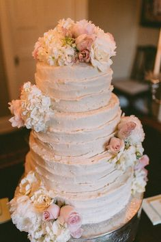 Three-tiered light pink buttercream-frosted wedding cake with ruffled frosting and fresh pink and white flowers {b. flint photography}