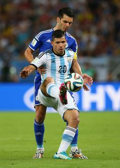 Sergio Aguero of Argentina holds off a challenge by Emir Spahic of Bosnia and Herzegovina during the 2014 FIFA World Cup Brazil Group F matc...