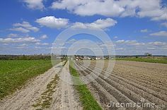 A country road among the fields with a view to a disant village, blue sky with scattered clouds in the background