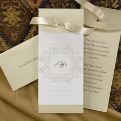 A layered invitation is created with a golden shimmer base card featuring your wedding verse and translucent overlay with a three initial monogram. All tied together with a satin taupe ribbon. Matching golden shimmer enclosures are sold separately.