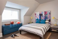 Contemporary bedroom boasts an eye-catching graffiti art headboard accenting a brown bed covered in gray awning stripe duvet paired with matching shams layered behind blue geometric pillows.