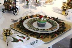mesa posta com jogo americano dourado, sousplat decorativo de natal, pratos estampados em verde e um lindo cupcake personalizado de natal ao centro em verde e dourado.