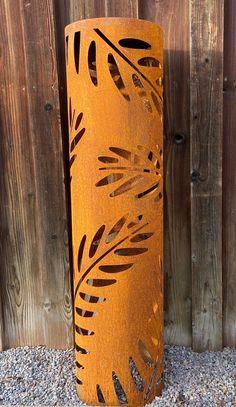 Dekorative Metallsäule mit Edelrostoptik für Ihren Garten. Diese Dekosäule hat rundherum schöne Farnblätter.