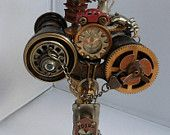 A Birds Secret View: This art piece is composed of a pair of opera glasses mounted on a candlestick on a wood footed stand. Opera glasses are decorated with clock gears, compasses, Bird wearing a thimble hat with a pinwheel and lots of miscellaneous charms and an old miniature pitcher. Opera glasses have a ceramic eye. Also a hanging dice off the birds ta