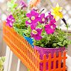 """""""A shelf outfitted with dollhouse fencing, both found at a crafts store and then painted orange, makes a delightful window box when planted with petunias and pinwheels."""""""