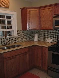 i love the glass tile back splash... i really think this would spice up my boring kitchen