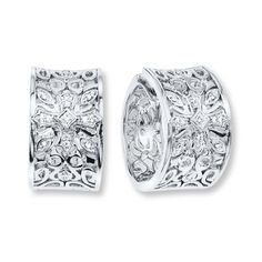 Exquisite detailing makes these hoop earrings a standout accessory for her. The sterling silver design is decorated with round diamonds, totaling 1/10 carat in weight. The earrings secure with hinged backs. Diamond Total Carat Weight may range from .085 - .11 carats.