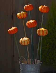 Tiny pumpkin torcheres: With a handful of garden stakes and some simple hardware, you can transform palm-size pumpkins into a bouquet of magical torcheres in minutes.