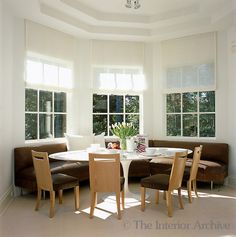 Vicente Wolf ~ The breakfast area takes advantage of a bay window and is furnished with a series of leather benches and Paris chairs around a glass-topped Saarinen Tulip table