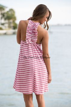 Stripes are always the right amount of detail! This cute stripe dress features a halter style with ruffle on the back, fuschia stripes, and lining underneath! You don't want to miss out on this so order quick!