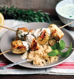 Rosemary Chicken Skewers with Sauce  INGREDIENTS 8 bamboo skewers 2 lbs boneless, skinless chicken breasts, cut into 2-inch pieces 3 tablespoons plus 1 tsp olive oil, divided 2 tablespoons minced fresh rosemary 1/2 cup lowfat plain yogurt Juice of 1/2 lemon 1 tablespoon finely chopped fresh mint, plus one spring for garnish (optional) 2 cups cooked brown rice (optional)