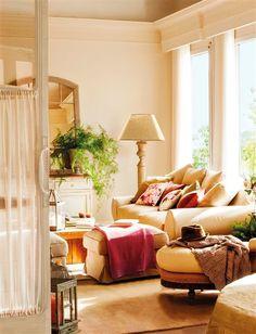 Salón con sofás y chaise longue en tonos crudos y espejo de cuarterones