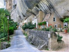 The village of Les Eyzies-de-Tayac-Sireuil, built on the site of prehistoric caves in Dordogne France. A recommended restaurant in one of the cliff homes.