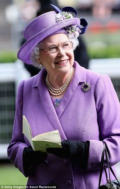 Queen Elizabeth could barely hide her delight after her horse won the race at Royal Ascot. She is shown wearing a lovely lavender ensemble along with a lavender hat & blue bow.