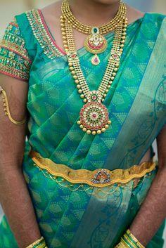 South Indian bride. Gold Indian bridal jewelry.Temple jewelry. Jhumkis. Teal blue green silk kanchipuram sari.Side braid with fresh jasmine flowers. Tamil bride. Telugu bride. Kannada bride. Hindu bride. Malayalee bride.Kerala bride.South Indian wedding.