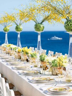 Awesome use of vases!!! Oh, I love this!!!  Large arrangement vases turned upside-down with sphere vases placed on their bases, filled with green hydrangea or cut bells of Ireland and tons of yellow oncidium orchid stems.  Gorgeous way to give height to a table! #tablescape #centerpiece