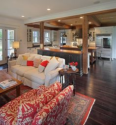 Modern farmhouse living room with bright pops of red, dark wood, rustic furniture pieces | KDW Home/Kitchen Designworks