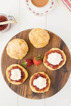 An overhead image of English scones with clotted cream and strawberry jam on a board