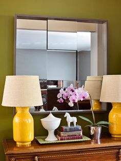 The subtle shifting in the square mirrors adds dimension and texture to what is typically a flat surface. The mirror has been hung on a green wall and positioned behind a wood table on which are two yellow lamps, a small silver bucket with pink orchids and a small green tray of knickknacks.