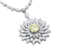 This floral pendant by Asprey has a brilliant cut yellow diamond at the centre and the surrounding petals are formed by individually cut diamonds, all set in platinum.  www.luxworldwide.com