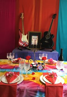For our 60s murder mystery party, we bought some colourful shawls from a charity shop and hung these on the wall and also used another shawl as a tablecloth.  Then we put some guitars on a covered bookcase and used a mini guitar and drum set as a table centrepiece.  We then folded some cheap red napkins and added a few flowers from the garden - and the result was some pretty groovy 60s party decorations!