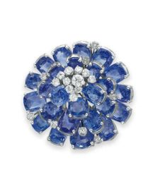 A SAPPHIRE AND DIAMOND BROOCH, BY CARTIER  Of circular outline, centering upon a cluster of circular-cut diamonds, to the concentric three tier cushion-cut sapphire plaque, interspersed with circular-cut diamonds, mounted in platinum and white gold