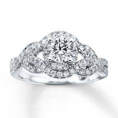 A captivating round diamond in this dazzling engagement ring will take her breath away. Additional pavé diamonds in romantic twists of 14K white gold complete the look. This fine jewelry ring has a total diamond weight of 1 carat. Diamond Total Carat Weight may range from .95 - 1.11 carats.