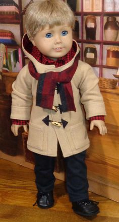 My boy is ready for school or play in his warm toggle-style coat, red and black check cotton shirt, and twill pants. The shirt is made with a straight collar, long sleeves with cuffs, and a front band with buttons and buttonholes. Sleeve cuffs close with snaps under button trim. The black cotton twill pants have front pockets, and a smooth front waistband with a bit of elastic at the back for easy fit. The toggle coat is an unlined 3/4 length wool coat with a lined hood. It has raglan…