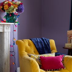 Mustard against purple living room chair and mantle with bright flowers in vase.