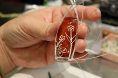 The making of a wire wrapped pendant - silver daisies on a red agate gems bead