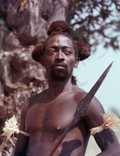 Africa | A Kuba hunter, ca. 1950, holds a spear and wears his hunting regalia, including armbands and a fur headdress. Kasai province, Belgian Congo (today DR Congo) | © Otto Lang